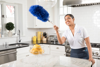 MaidPro employee dusting a light fixture in a kitchen.