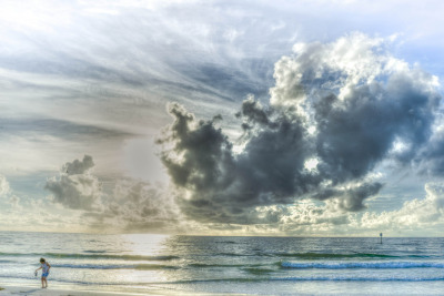 Bay County Florida, clearwater beach with a child playing and lovely clouds.