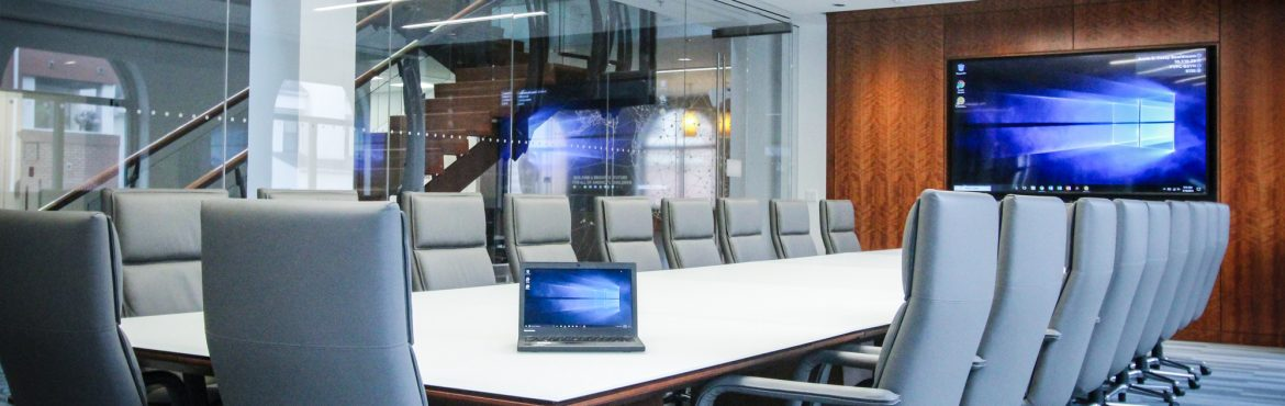 Cenero Non-Profit Boardroom. A large meeting table with chairs all around and a large tv screen at the end of the room.