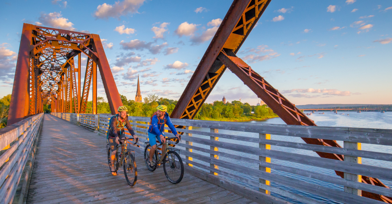 Fredericton, New Brunswick. Two cyclists riding over a bridge with a blue sky and scattered clouds behind.