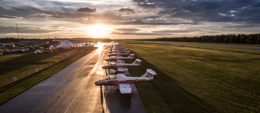 Moose Jaw Saskatchewan photo of Snowbirds airplanes on the runway with the sun setting behind them.
