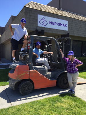 Merrimak Capital Company LLC Mak and the resale team outside by a forklift.