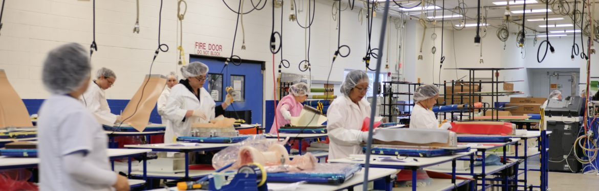 AIM Aerospace production lines with multiple people wearing hair nets at workstations with cables hanging down from the ceiling powering tools.