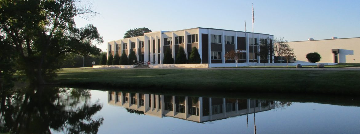 American Metal Technologies building with water in front.