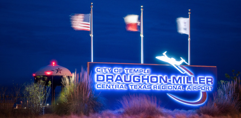 Daughon-Miller Central Texas Regional Airport sign lit up at night with flags above it blowing.