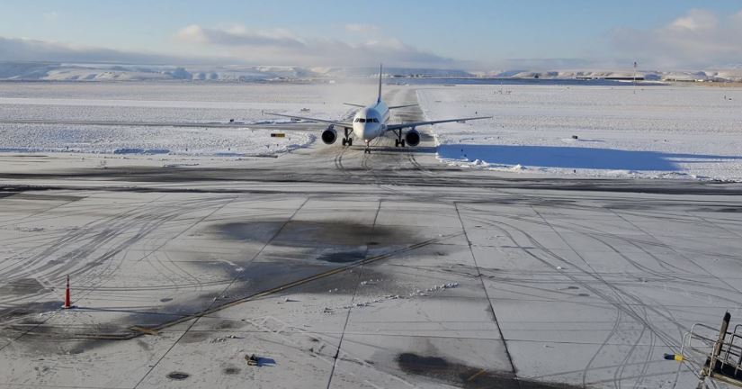 Lewiston-Nez Perce County Regional Airport, commercial jet taxiing in on a snowy runway.