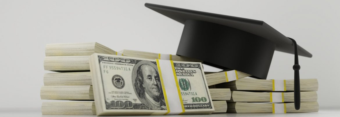 Bank wrapped hundred dollar bills stacked with a graduation cap on top.
