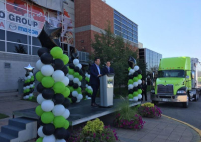 Sault St Marie, Ontario. Event with two men speaking at a podium with balloon displays around the stage.