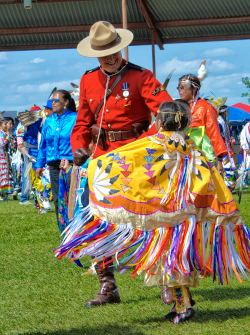 Wetaskiwin Alberta, powwow with colorful Native America Indian clothing and a small child dancing with a uniformed man.