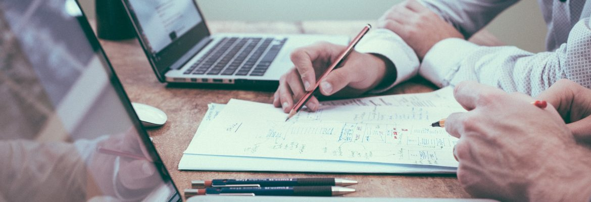 Great Resumes Fast Executive Writing Tips for 2019. Two people sitting at a table with laptops and pen and paper.