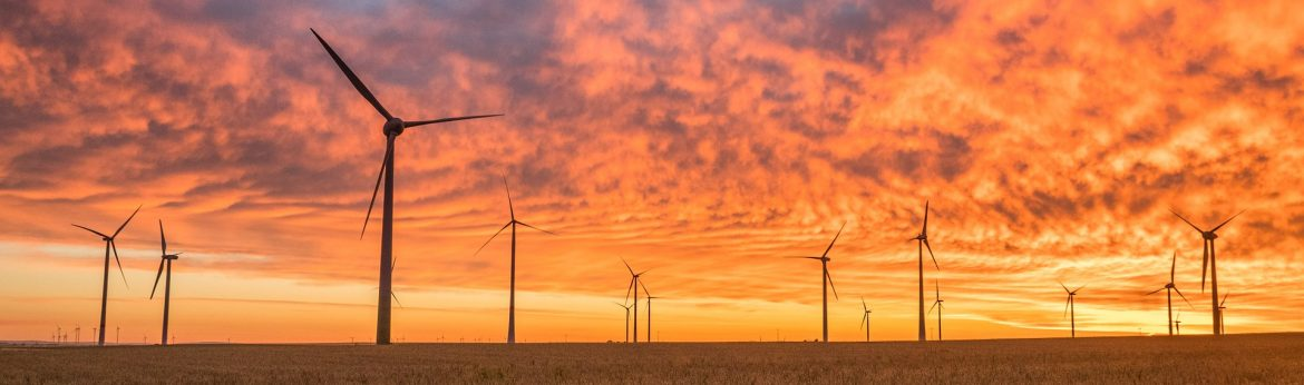 5 / energyby5 A field of wind turbines with an orange sky behind.