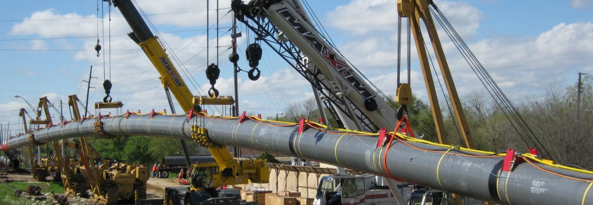 Arceneaux Wilson & Cole LLC. A long pipe being installed with multiple cranes holding it up in the air.