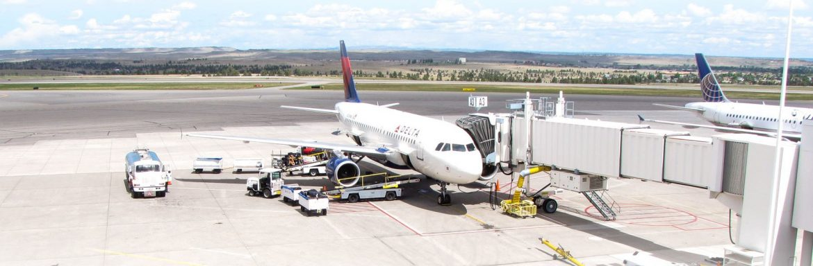 Billings Logan International Airport; Passenger Jet refueling and loading cargo and passengers at the terminal.