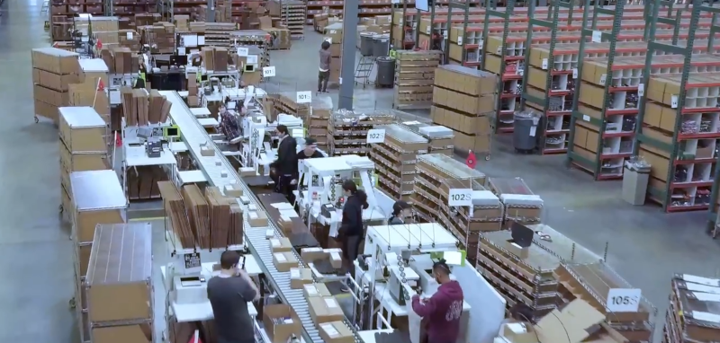 Enlinx workers at work in a large warehouse.