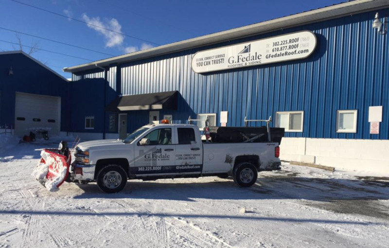 G. Fedale roofing & siding building in winter with a truck that has a snowplow on front.