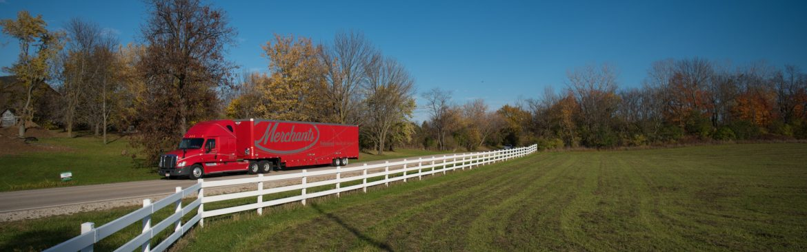 Merchants Moving and Storage semi truck traveling through a green field on a road with a white fence and trees behind.