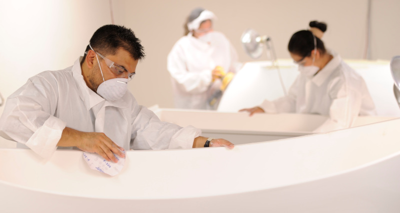 Clarke Products Inc. employees sanding bathtubs.