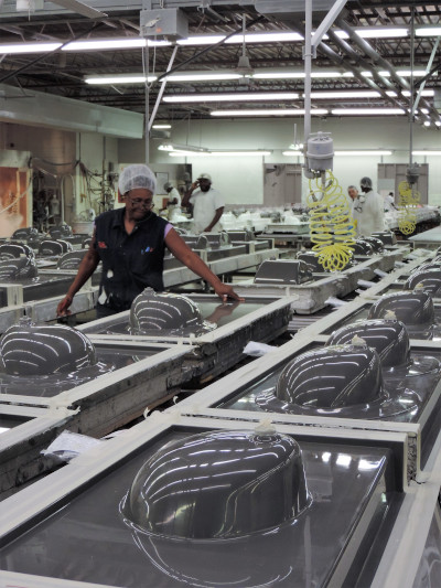 The International Cast Polymer Association. Factory with upside sinks being worked on by employees.