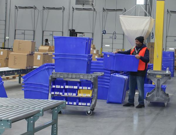 Future Forwarding Company warehouse employee moving blue totes.