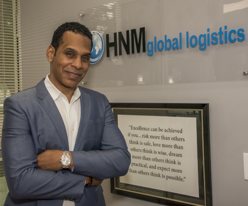 HNM Global Logistics CEO Tony McGee standing in front of a company sign and a framed quote.