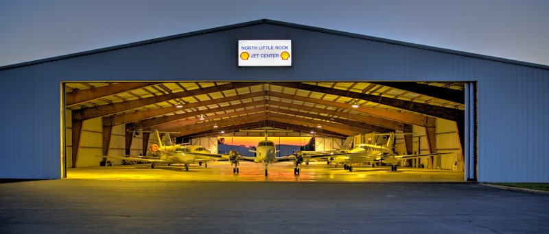 The North Little Rock Municipal Airport Jet Center hangar at night with aircraft inside.