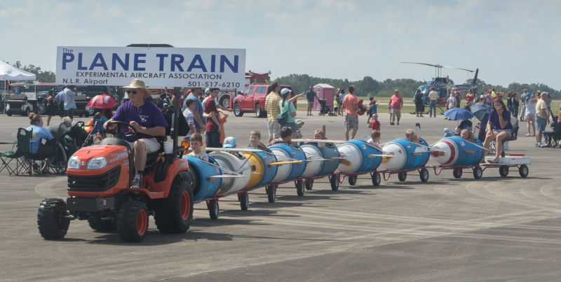 The North Little Rock Municipal Airport Plane Train with kids riding behind a tractor in cars that look like airplanes.
