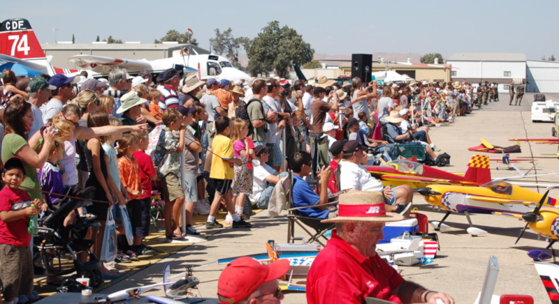 Paso Robles Municipal Airport; a large crows at an airshow with model airplanes on the ground on the right side.