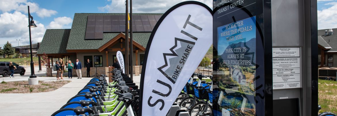 Summit County, Utah Summit bike share sign with bikes lined up in a row behind and a building with solar panels on the roof in the background.