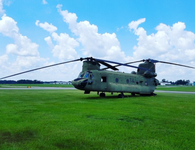 Tuscaloosa Regional Airport, military helicopter in the grass. Blue sky and puffy white clouds behind.