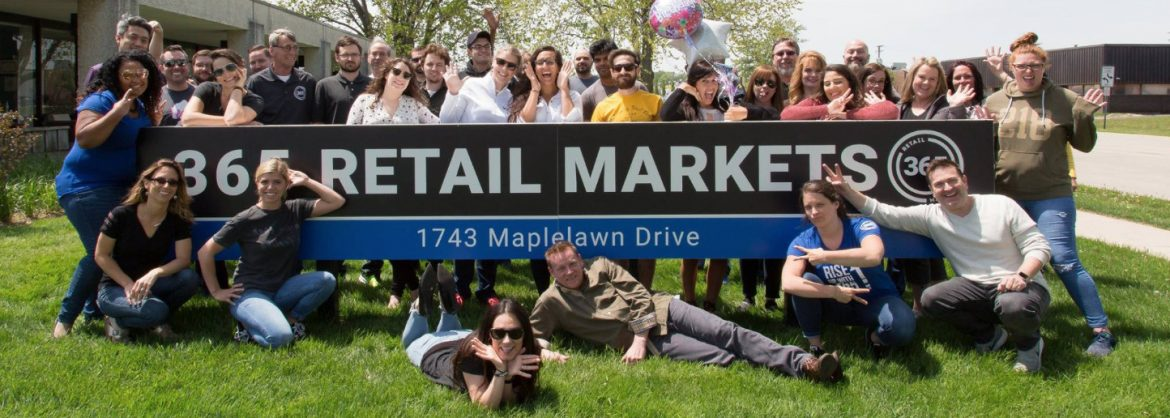 365 Retail Markets team photo by their sign.