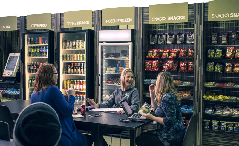 365 Retail Markets; 3 people sitting at a table with different shelves and refrigeration units along the wall behind with drinks and snacks.