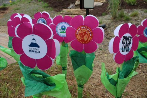 Asheville, North Carolina paper flowers on grass. One has the city name and another says River Link.