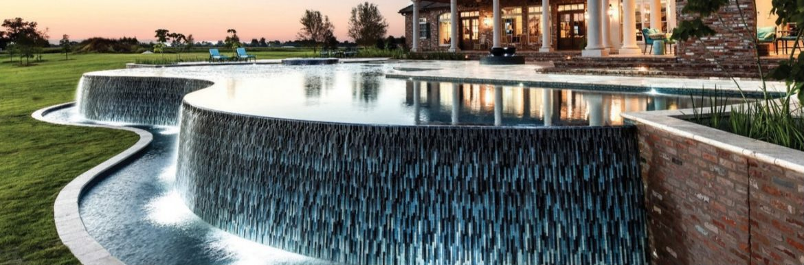 A great photo of a pool with water flowing over the edges of the pool with green grass near. The Association of Pool & Spa Professionals