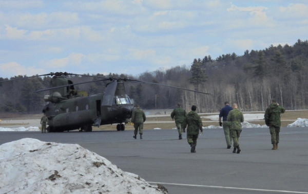 Auburn-Lewstion Airport Chinook helicopter with crew walking towards it on the runway.