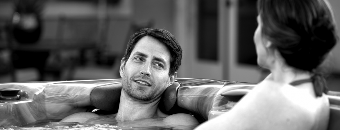 A man and woman in a hot tub, black and white photo. MAAX Spas.