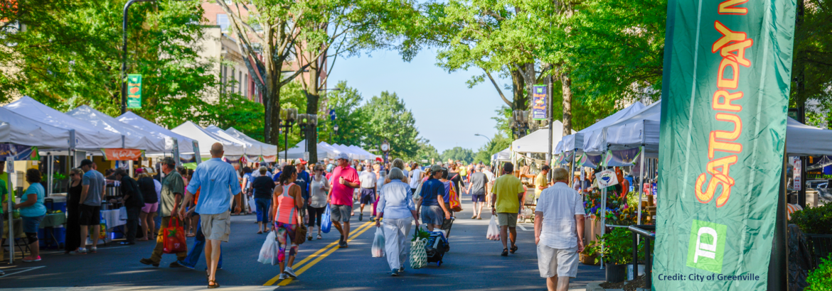 Municipal Association of South Carolina; A view of the City of Greenville's Saturday Market on a street lined with vendor tents.