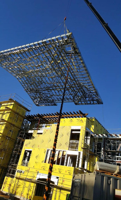 Superior Wall Systems construction site with a large roof section being moved into place with a crane.
