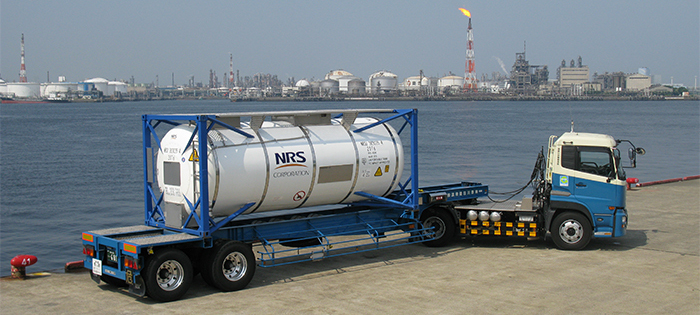 NRS Logistrics Inc, ISO Tank Container on a truck in front of a body of water.