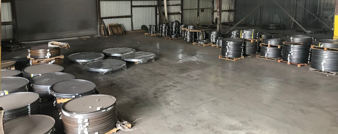 Shamrock Steel floor of warehouse with stacks of round steel parts.