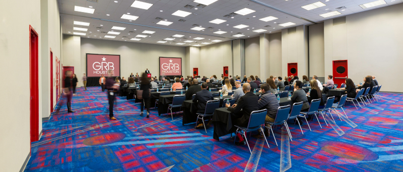 Large conference room with rows of chairs and people at the George R Brown Convention Center Avenida Houston.