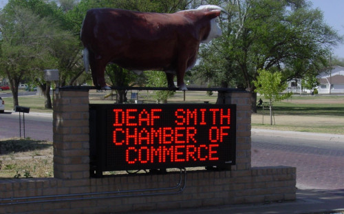 Deaf Smith County Texas Chamber of Commerce sign with red light lettering and a cow on top.
