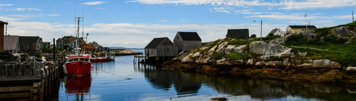 Louisbourg Seafoods, Limited. View of a bay with buildings, boats and docks.