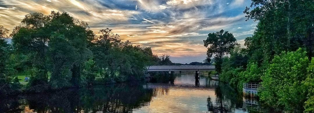 Millville, New Jersey, NJ city park with a river and bridge going over it and cloudy bright lit sky.