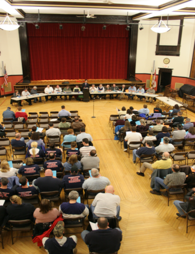 A group of people having a town meeting for Farmington New Hampshire in 2007.