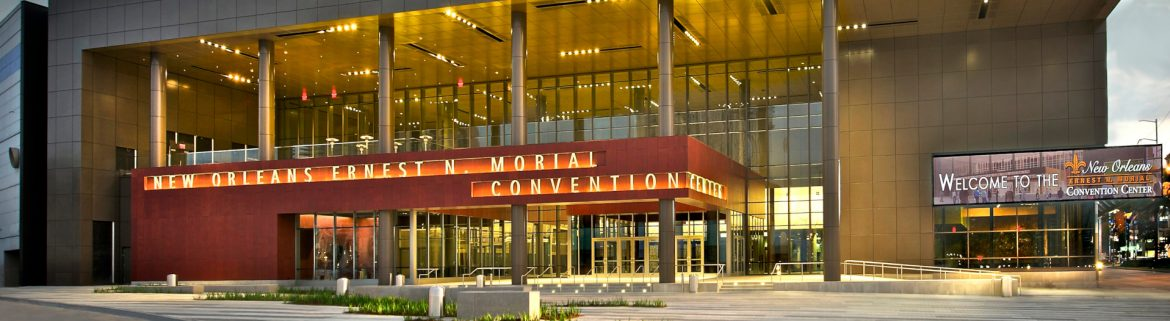 New Orleans Ernest N. Morial Convention Center front entrance with some daylight left but lights on and glowing. Cloud and blue sky visible in background.