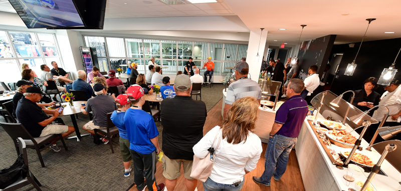 Richmond Raceway Complex event photo showing two men on one side of the room with a microphone and people sitting and standing with catering on the right.