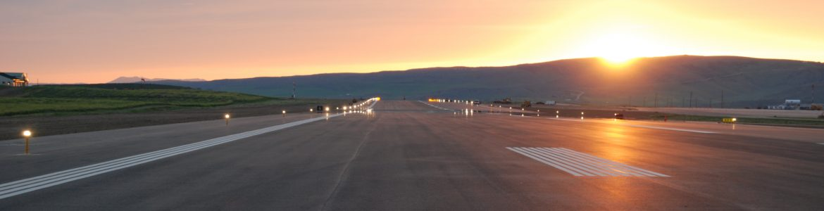 Yampa Valley Regional Airport runway at sunset with the sun peaking over a mountain in the background.