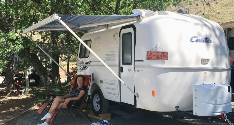 Casita Enterprises Inc., a woman sitting outside of her set up camper complete with awning.