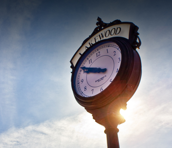Lakewood Township, New Jersey clock on a pole with the sun glinting partially behind.