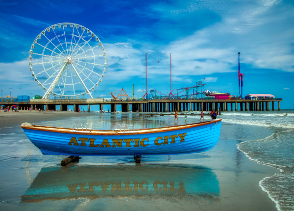 New Jersey Economic Development Authority Atlantic City from the beach looking at a blue boat on the sand with Atlantic City written on the side and the boardwalk with a Ferris wheel behind.